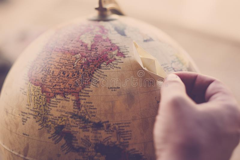 Planet earth on sphere with hand and little paper boat for travel and dream concept - move around the world with cruise ship and royalty free stock photography