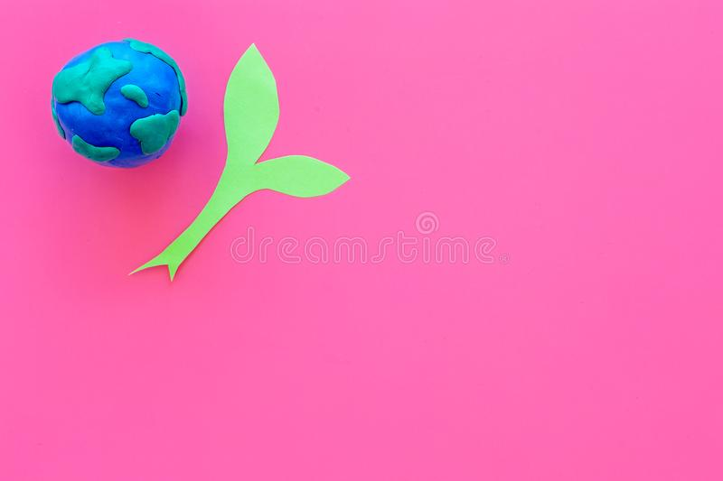 Planet, ecology. plastiline symbol of planet Earth globe and plant coutout on pink background top view copy space. Planet, ecology. plastiline symbol of planet royalty free illustration