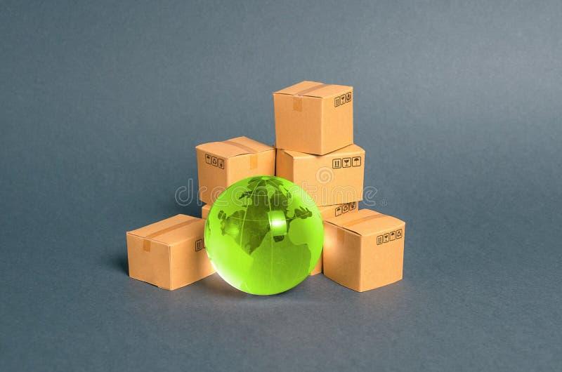 Planeta de vidrio verde y un montón de cajas de cartón. Empresa e industria, infraestructura de transporte. El concepto de comer imagen de archivo