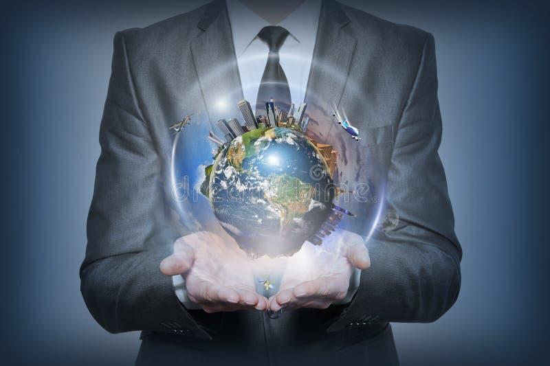 Planetenerde in den menschlichen Händen auf blauem Hintergrund lizenzfreie stockfotografie