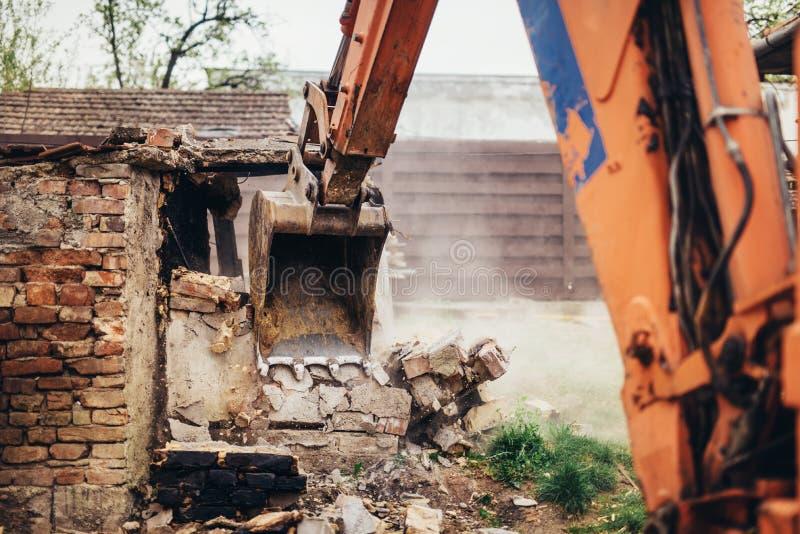 Planierraupe, die einen Altbau an der Baustelle zerquetscht stockbild