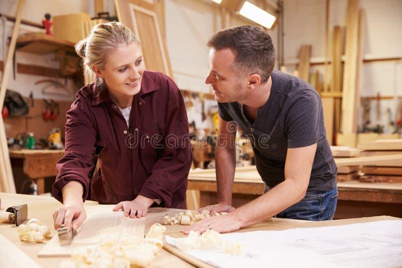 Planierungsholz Tischler-With Female Apprentices in der Werkstatt stockfotografie