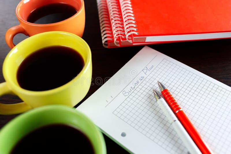 Planificación de empresas con café, el cuaderno, el sketchbook y la pluma dos en la tabla de madera del marrón oscuro imagen de archivo libre de regalías