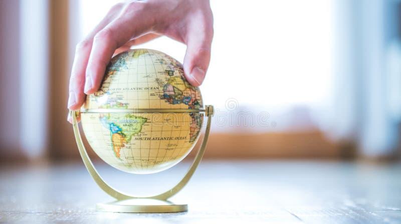 Planificación del viaje siguiente: el globo miniatura en el piso de madera, da el tacto de él fotografía de archivo