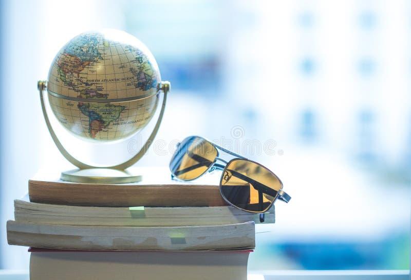 Planificación del viaje siguiente: Globo y gafas de sol miniatura en una pila de libros imágenes de archivo libres de regalías