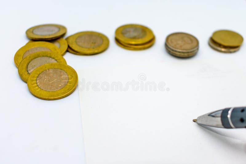 Planificación financiera con monedas y una pluma en un fondo blanco fotografía de archivo
