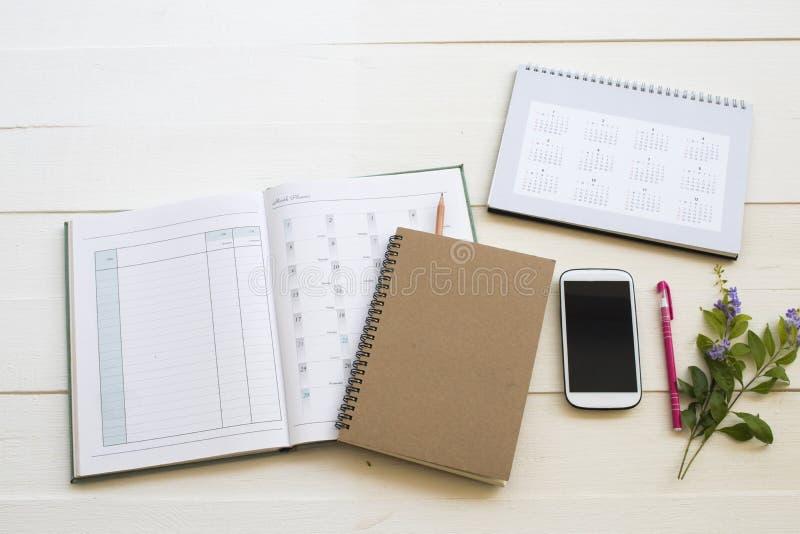 Planificador de la cuenta del cuaderno, calendario y teléfono móvil para el trabajo del negocio foto de archivo libre de regalías