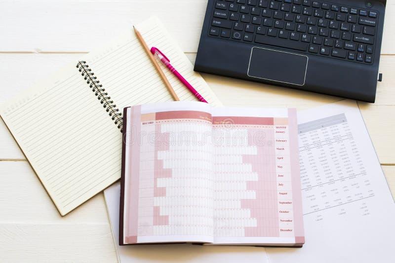 Planificador de la cuenta del cuaderno, ordenador y estado financiero para el trabajo del negocio imágenes de archivo libres de regalías