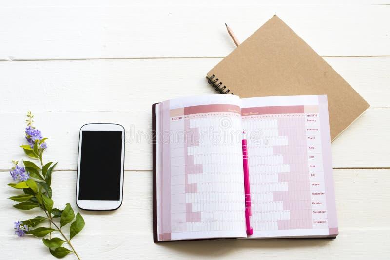Planificador de la cuenta del cuaderno y teléfono móvil para el trabajo del negocio imágenes de archivo libres de regalías