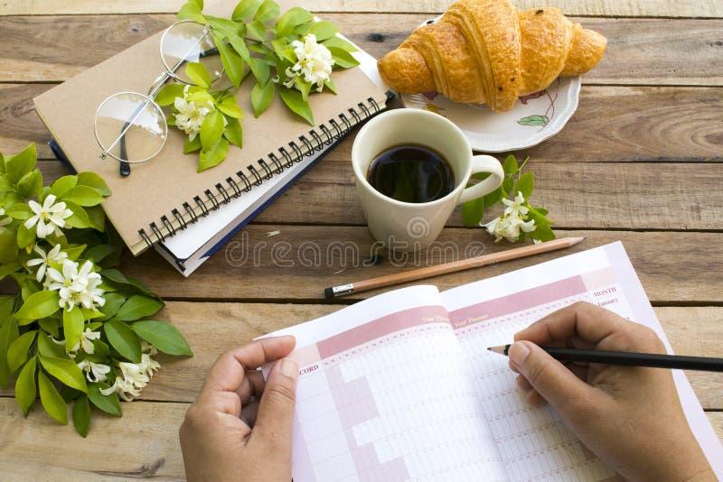 Planificador del año del proyecto del cuaderno para el trabajo del negocio con la mano del trabajo de la escritura de la mujer imagen de archivo