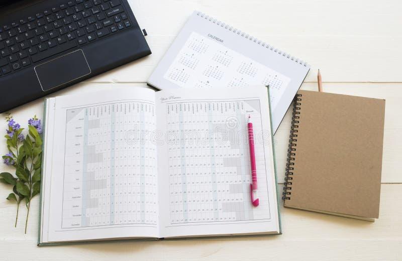 Planificador del cuaderno, calendario, ordenador para el trabajo del negocio imagen de archivo