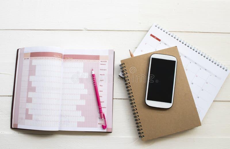 Planificador del cuaderno, calendario y teléfono móvil para el trabajo del negocio fotos de archivo