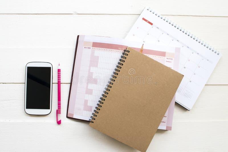 Planificador del cuaderno, calendario y teléfono móvil para el trabajo del negocio imágenes de archivo libres de regalías