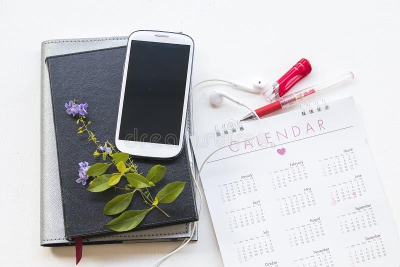 Planificador del cuaderno con el calendario y teléfono móvil para el negocio fotos de archivo libres de regalías