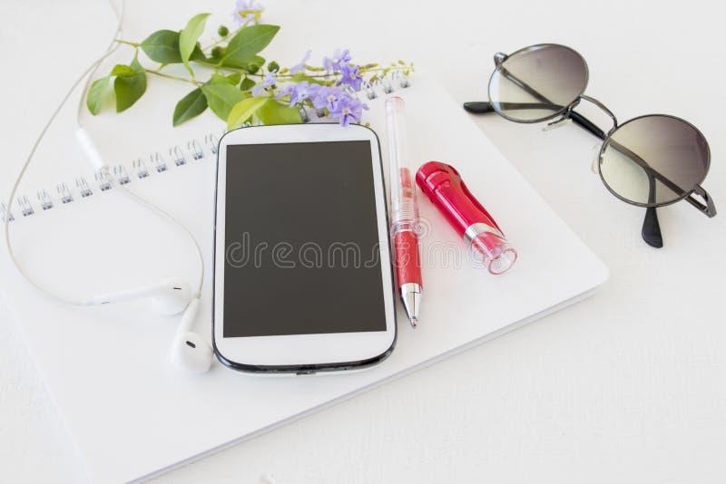 Planificador del cuaderno con el calendario y teléfono móvil para el negocio fotos de archivo