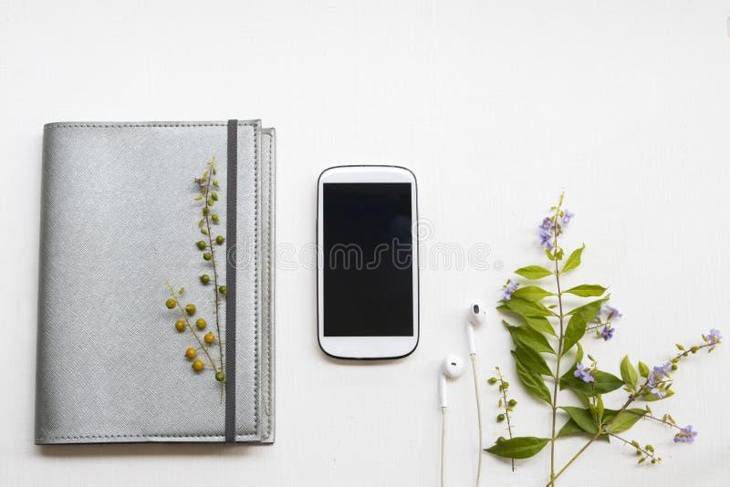 Planificador del cuaderno con el teléfono móvil para el trabajo del negocio y las flores púrpuras imágenes de archivo libres de regalías