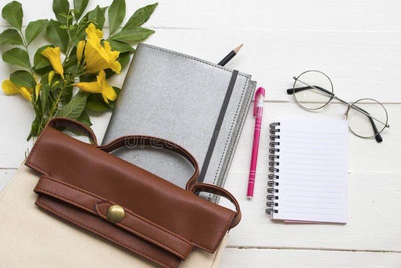 Planificador del cuaderno para el trabajo del negocio con el bolso, las gafas y la flor fotografía de archivo
