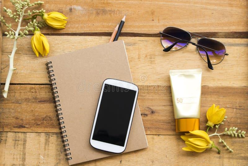 Planificador del cuaderno, teléfono móvil para el trabajo del negocio con el ylang del ylang de la flor foto de archivo