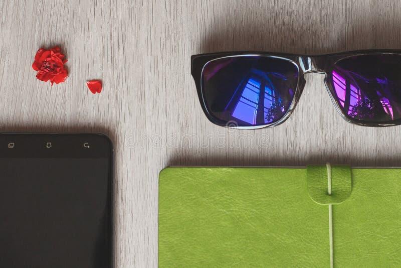 Planificador del cuaderno, teléfono móvil y bolso rosado de la trabajadora de la forma de vida para el negocio en el escritorio d fotografía de archivo