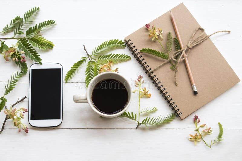 Planificador del cuaderno, tel?fono m?vil para el trabajo del negocio con el ylang del ylang de la flor fotos de archivo