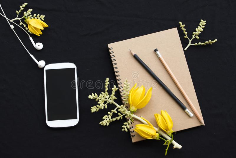 Planificador del cuaderno, tel?fono m?vil para el trabajo del negocio con el ylang del ylang de la flor fotos de archivo libres de regalías