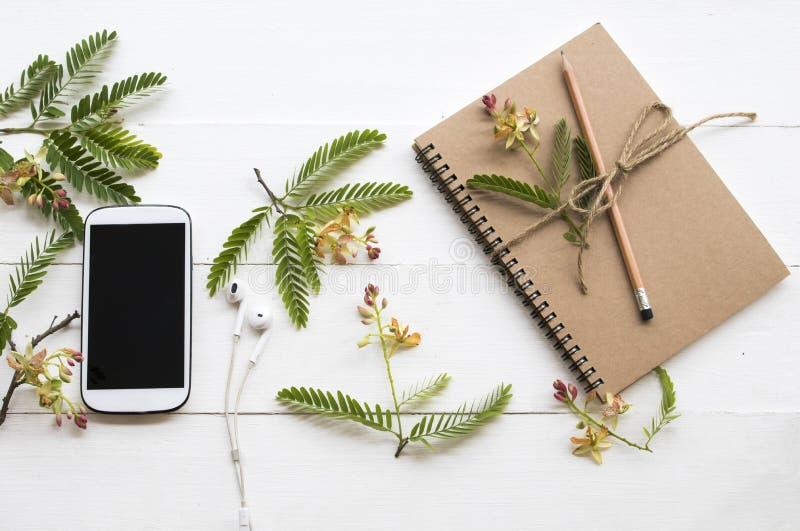 Planificador del cuaderno, tel?fono m?vil para el trabajo del negocio con el ylang del ylang de la flor fotografía de archivo libre de regalías