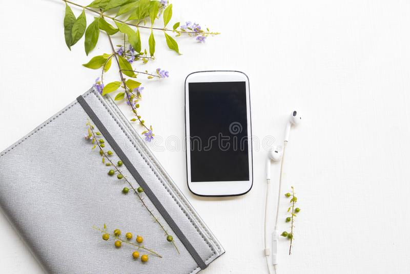 Planificateur de carnet avec le téléphone portable pour le travail d'affaires et les fleurs pourpres images stock