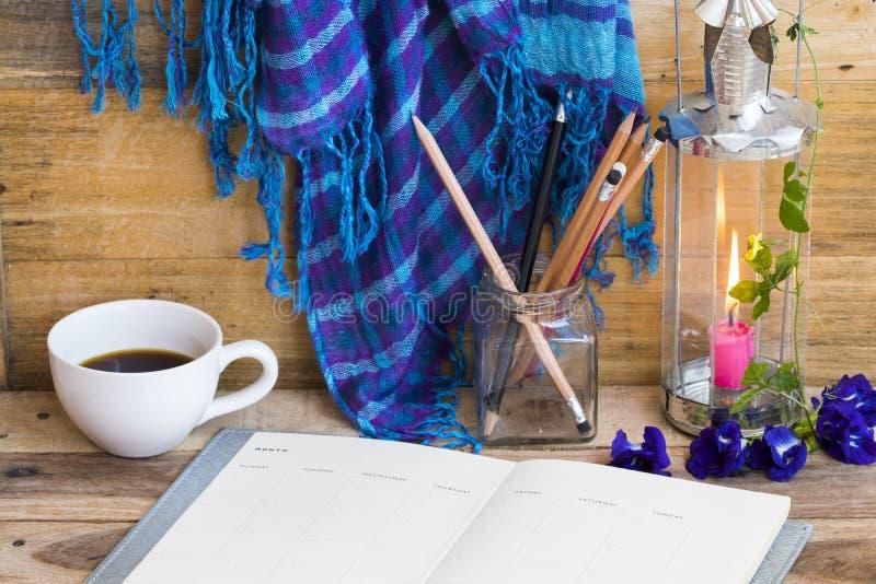 Planificateur de portables pour le travail d'affaires avec café chaud, foulard bleu, lampadaire et fleurs de vie femme se détendr photo stock
