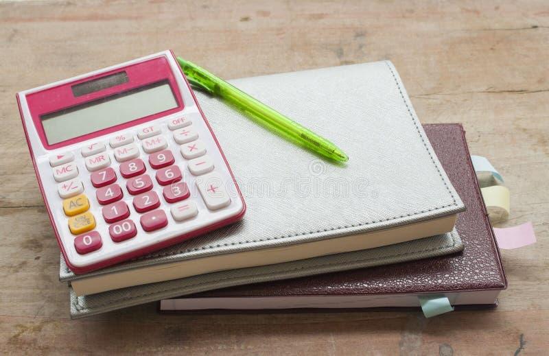 Planificateur et calculatrice mensuels de carnet pour financier au bureau images stock