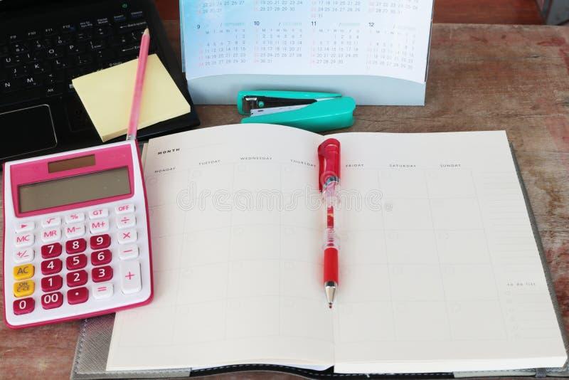 Planificateur et calculatrice mensuels de carnet pour financier au bureau photos libres de droits