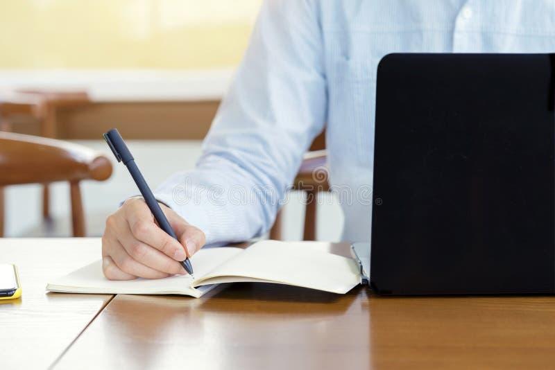 Planification d'homme d'affaires ?crivant la note et fonctionnant avec l'ordinateur portable sur le bureau ?crivant ? quelque cho photographie stock