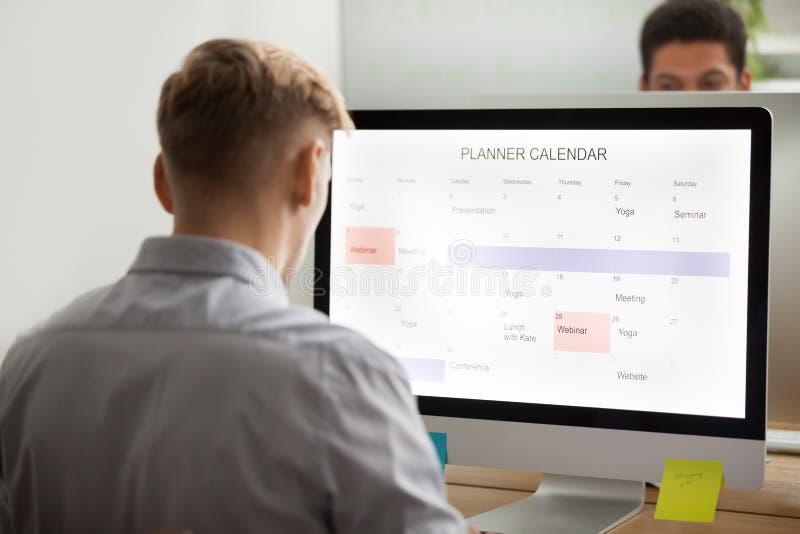 Planification d'homme d'affaires faisant le programme sur l'applica de planificateur d'ordinateur photos libres de droits