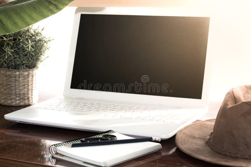 Planification de vacances d'aventure sur l'ordinateur Tableau avec le chapeau occidental, usine, carnet, crayon images stock