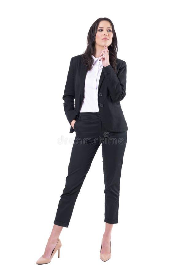 Planification réussie sérieuse sûre de femme d'affaires et pensée avec la main sur des regards de menton loin photo stock