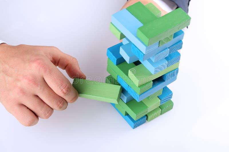 Planification, risque et stratégie dans les affaires, homme d'affaires sortant un bloc en bois d'une tour photographie stock