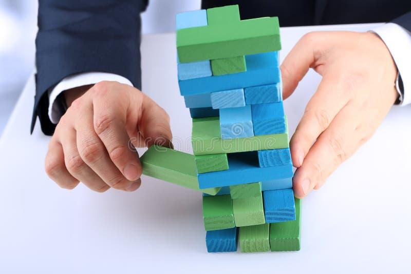 Planification, risque et stratégie dans les affaires, homme d'affaires sortant un bloc en bois d'une tour images stock