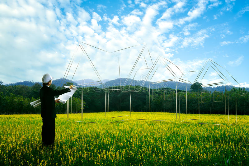 Planing. Civil engineer planing at empty landscape with house building drawing in background royalty free stock photo