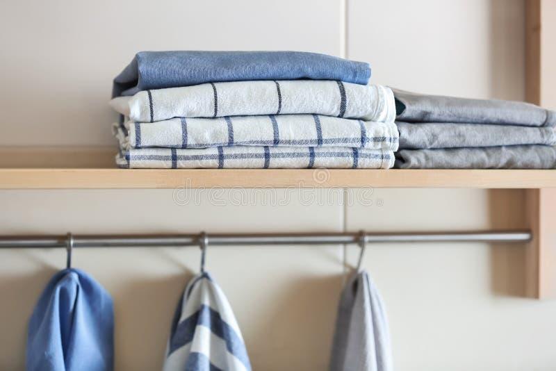 Plank en rek met schone keukenhanddoeken stock afbeeldingen