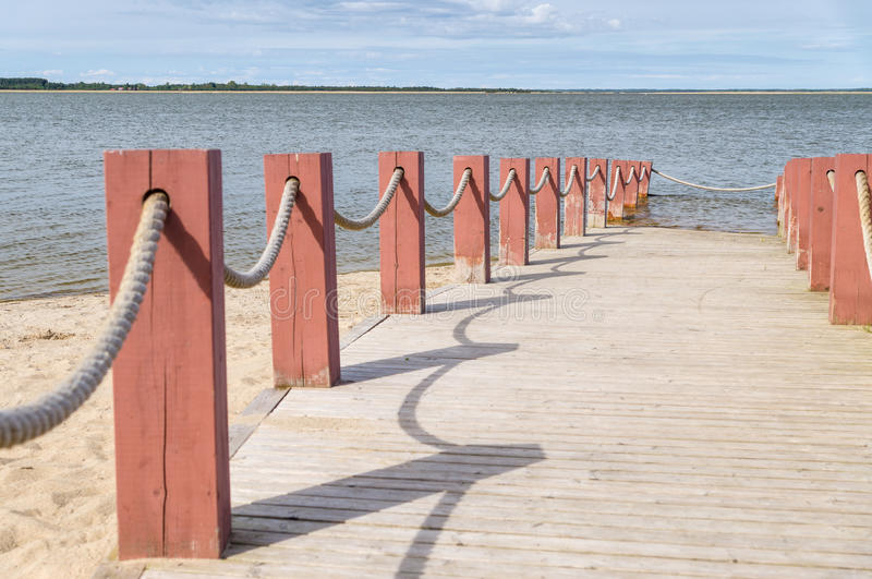 Plank footpath and fence boundary rope barrier on the beach. Plank footpath and red fence boundary rope barrier on the beach royalty free stock image