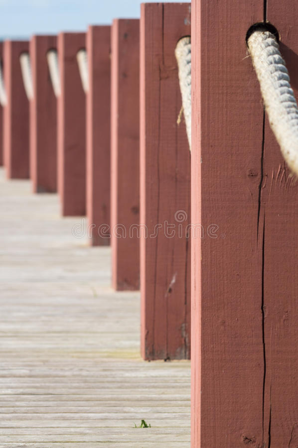 Plank footpath and fence boundary rope barrier closeup. Plank footpath and red fence boundary rope barrier closeup stock images