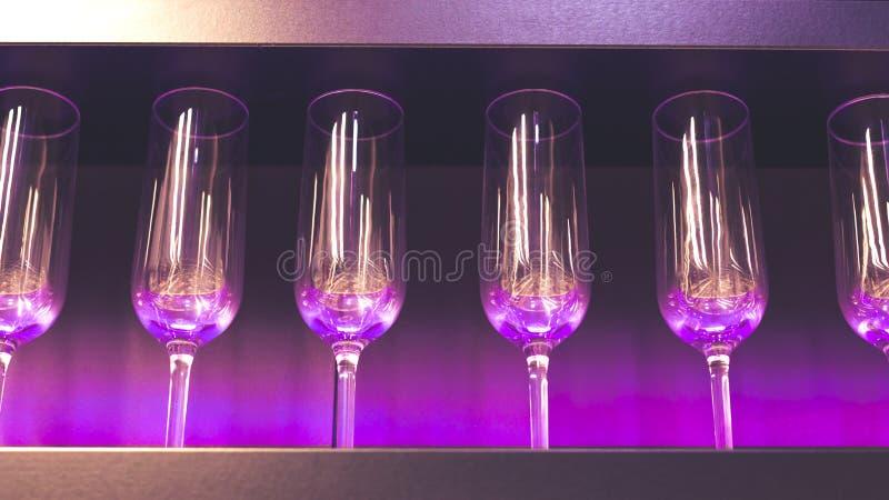 Plank met heel wat lege wijnglazen met roze en violet licht Bar of glaswerkwinkelbinnenland Viering, gebeurtenis of royalty-vrije stock afbeelding