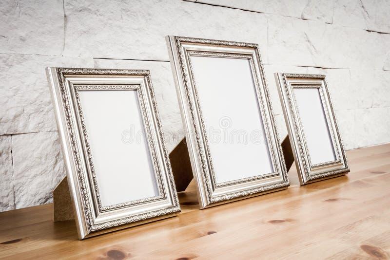 Plank met kaders en witte muur royalty-vrije stock foto