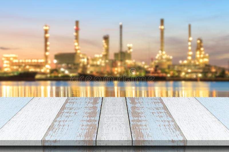 Plank wood or table top with blurred Oil refinery plant background. royalty free stock image