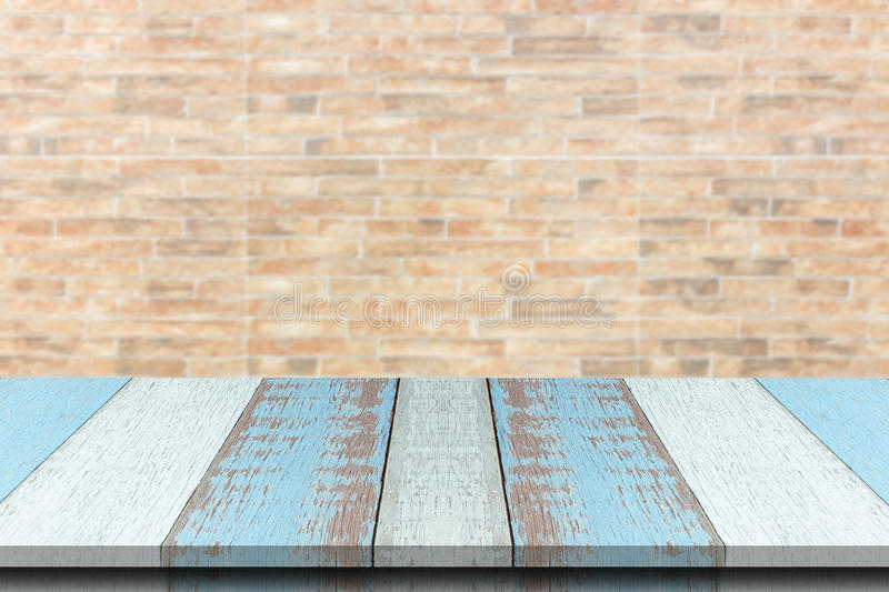 Plank wood or table top with blurred synthetic wall brick background. royalty free stock photo
