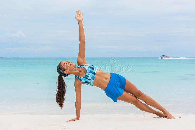 Planka för sida för flicka för övningskonditionyoga utbildande på stranden Plank för kvinna för kärnakroppgenomkörare i den blåa  royaltyfria foton