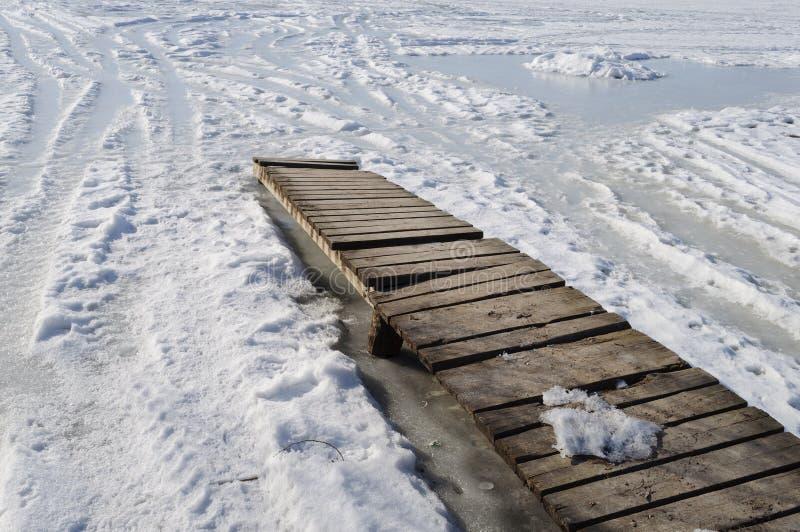 Planked spång på det djupfrysta dammet fotografering för bildbyråer