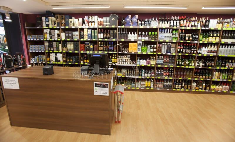 Planken met flessen Het opschorten, winkel en contant geld royalty-vrije stock afbeelding