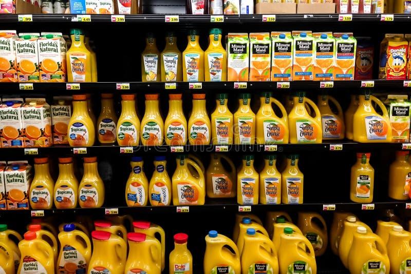 Planken met vele flessen jus d'orange in kruidenierswinkelopslag royalty-vrije stock foto's