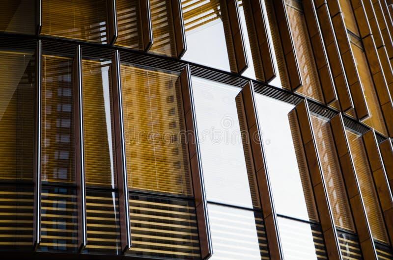 Planlägg det fyrkantiga glass fönstret på högväxt byggnad i guling arkivfoton