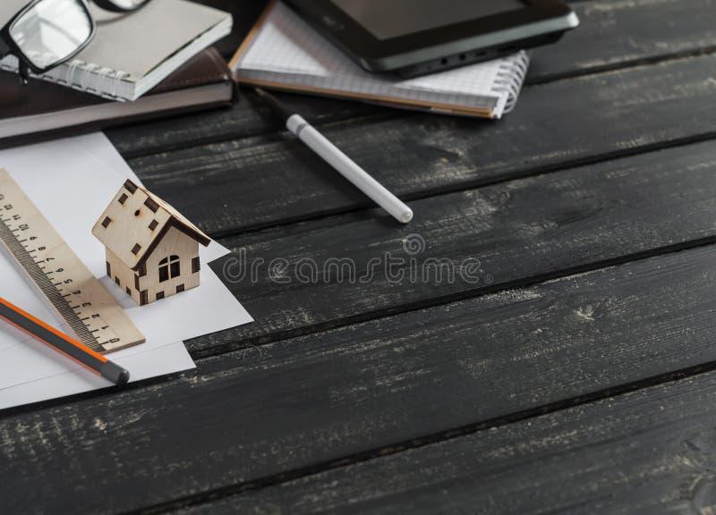 Planläggning av konstruktionen av ett hus Kontorsskrivbord med affärsobjekt - öppen anteckningsbok, minnestavladator, exponerings royaltyfri foto